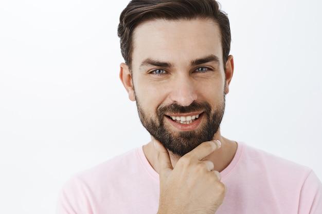 ピンクのtシャツで表現力豊かなひげを生やした男