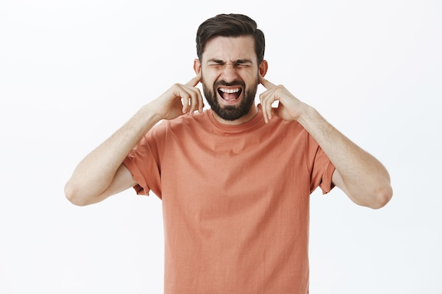 Expressive bearded man in orange tshirt Free Photo