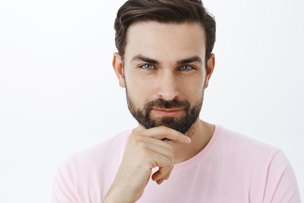 Uomo barbuto espressivo in maglietta rosa