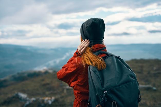 屋外の自然とポーズをとる表現力豊かな美しい旅行者