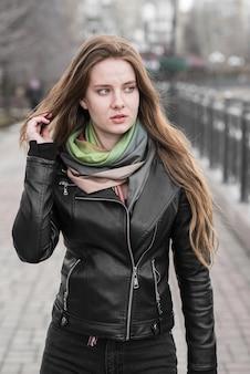 Выразительная красивая молодая женщина позирует на открытом воздухе