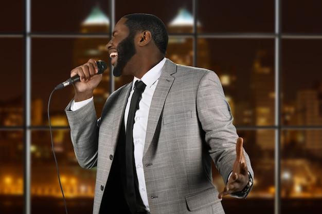Выразительный черный певец с микрофоном.