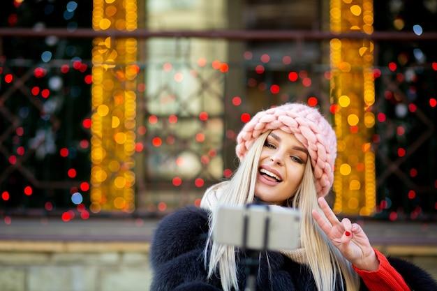 花輪で飾られた街の通りで自分撮りをしながら、ピンクの帽子をかぶった表情豊かな金髪モデル。テキスト用のスペース
