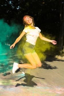 彼女の周りに爆発する鮮やかな色でジャンプする表現力豊かなブロンドの女性