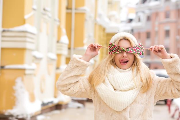 彼女の顔の近くにおいしいクリスマスキャンディーを持って、暖かいニット帽をかぶった長い髪の表情豊かなブロンドの女性