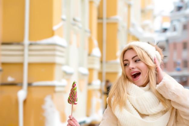 カラフルなクリスマスのお菓子を楽しんで、白いニット帽とスカーフを身に着けている長い髪の表現力豊かなブロンドの女性
