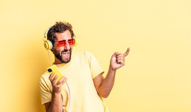ヘッドフォンとsartphoneで音楽を聴いている表現力豊かな狂気のひげを生やした男