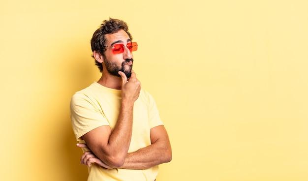 黄色の壁にコピースペースを持つサングラスを身に着けている表現力豊かな狂気のひげを生やした男