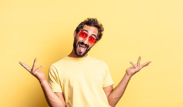 노란 벽에 복사 공간이 있는 선글라스를 끼고 있는 미친 수염 난 남자