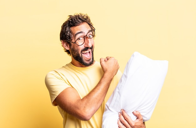 Expressive crazy man feeling happy and facing a challenge or celebrating and holding a pillow