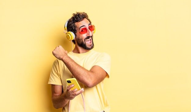 Expressive crazy man feeling happy and facing a challenge or celebrating with headphones