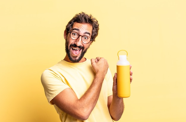 Expressive crazy man feeling happy and facing a challenge or celebrating with a tea thermos
