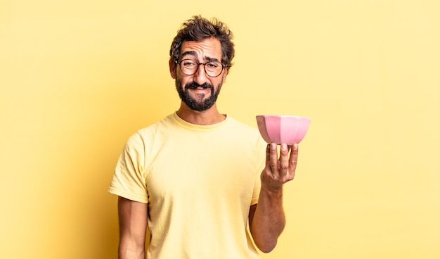 Expressive crazy man feeling sad and whiney with an unhappy look and crying and holding a pot