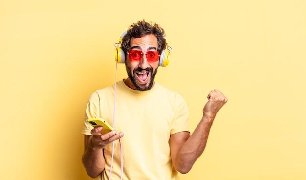 ショックを受け、笑い、ヘッドフォンで成功を祝う表現力豊かな狂気の男
