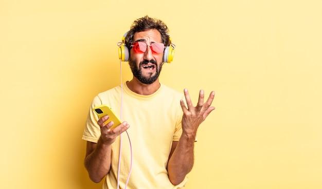 ヘッドフォンで必死になって欲求不満とストレスを感じている表現力豊かな狂気の男
