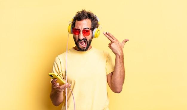 不幸でストレスを感じている表情豊かな狂気の男、ヘッドフォンで銃のサインを作る自殺ジェスチャー