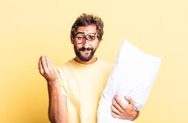 표현력 있는 미친 남자가 캐피시나 돈 제스처를 하고, 지불하라고 말하고 베개를 들고 있습니다.