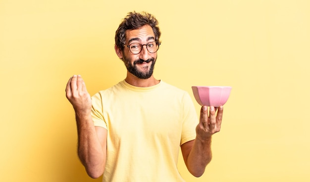 표현력이 풍부한 미친 남자가 capice 또는 돈 제스처를 만들고, 지불하라고 말하고 냄비를 들고 있습니다.