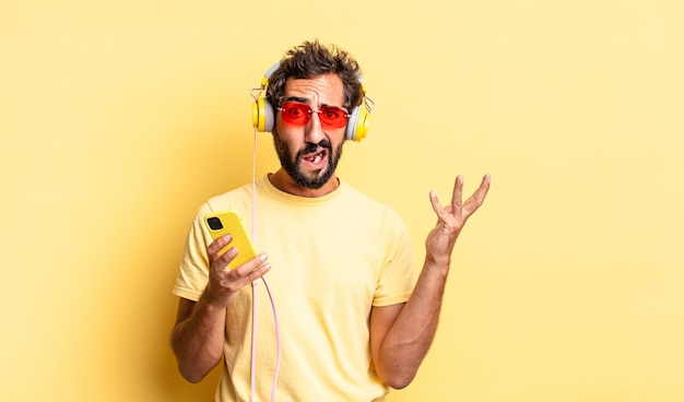 Expressive crazy man screaming with hands up in the air with headphones