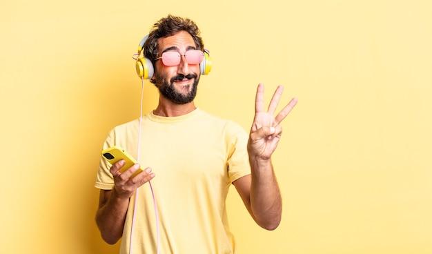 Выразительный сумасшедший мужчина улыбается и выглядит дружелюбно, показывая номер три в наушниках