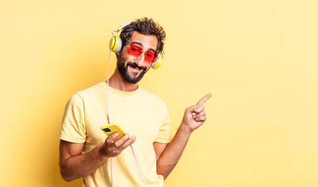 元気に笑って、幸せを感じて、ヘッドフォンで横を指している表現力豊かな狂気の男