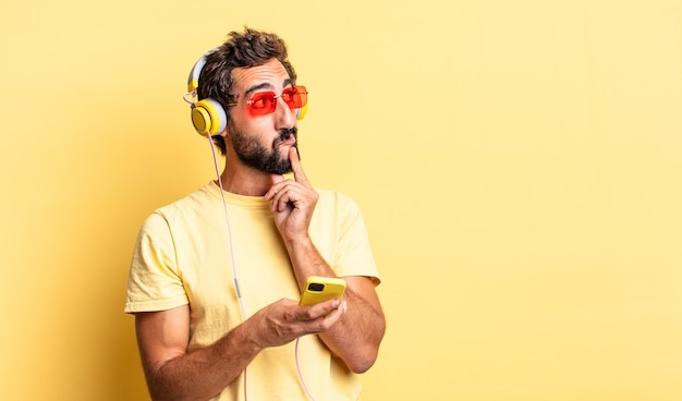 Expressive crazy man smiling happily and daydreaming or doubting with headphones