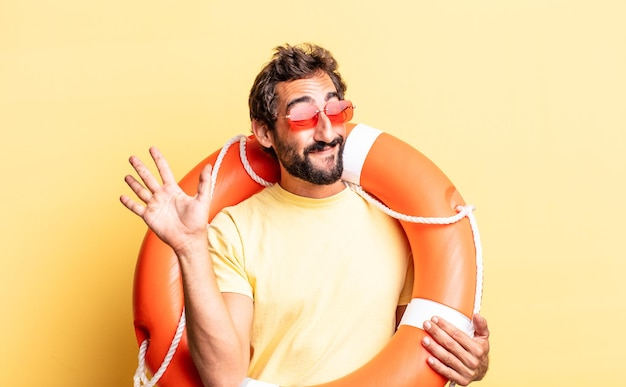 Expressive crazy man smiling happily, waving hand, welcoming and greeting you. life guard concept