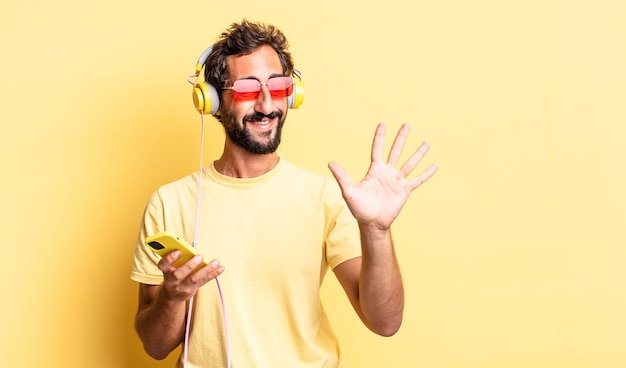 Expressive crazy man smiling and looking friendly, showing number five with headphones