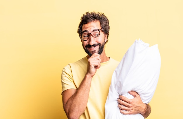 Expressive crazy man smiling with a happy, confident expression with hand on chin and holding a pillow