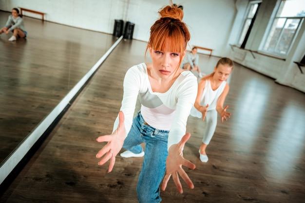 表現力豊かなダンス。赤毛のバレエ教師とその生徒が踊りながら表情豊かに感じる Premium写真