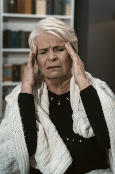 Expressive elderly blonde feels a headache from stress