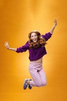 Expressive and enthusiastic carefree friendly joyful redhead woman in purple sweater and pants jumping joyfully with raised hands smiling yelling from happiness and joy against orange background