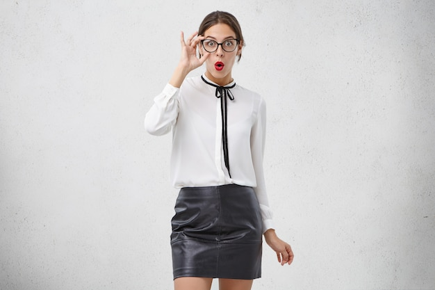 Expressive facial emotions concept. shocked female teacher in fashionable glasses