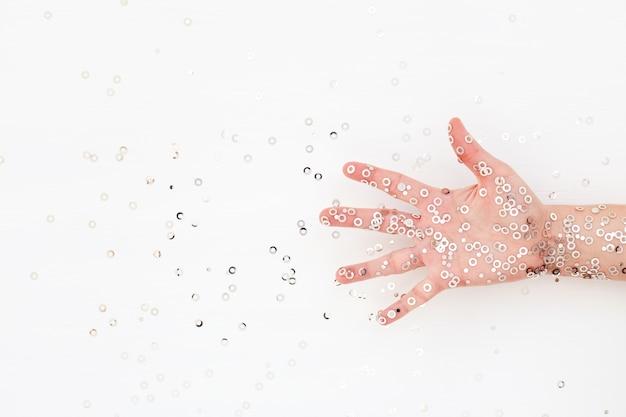 白い表面にシルバーの輝き紙吹雪で表現力豊かな女性の手のひら