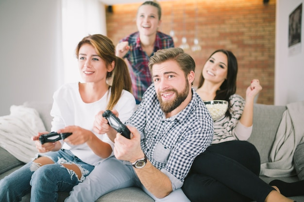 Expressive friends playing game on sofa