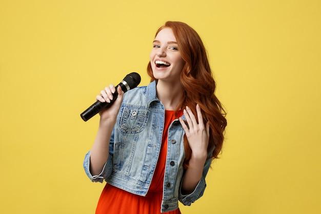 Выразительная девушка петь с микрофоном, изолированных ярко-желтый фон.