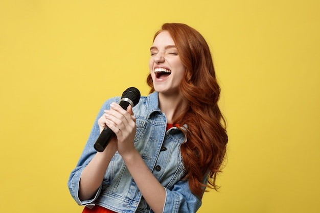 Expressive girl singing with a microphone, isolated bright yellow background.