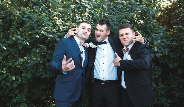 Expressive groomsmen posing in park