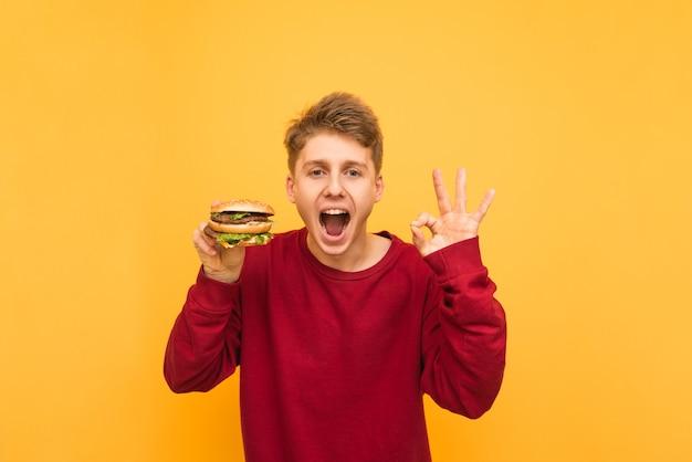ハンバーガーを手に持った表情豊かな男がokサインを表示し、黄色のカメラを見る