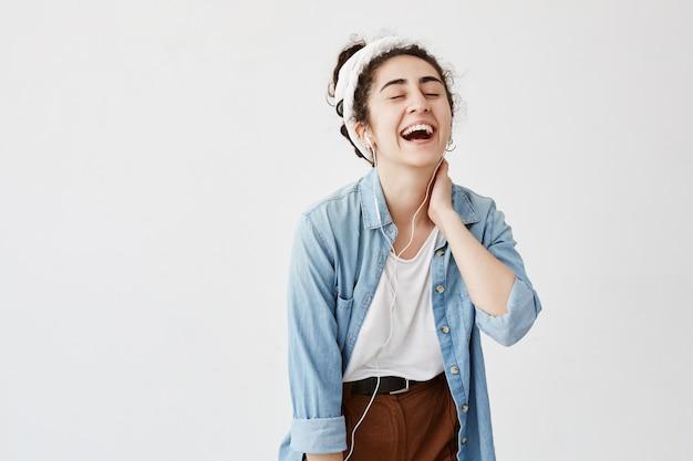 Выразительная счастливая эмоциональная девушка с темными и вьющимися волосами в пучке, слушает музыку в наушниках, наслаждается приятными мелодиями, имеет хорошее настроение, отдыхая в помещении. люди, отдых, образ жизни, красота.