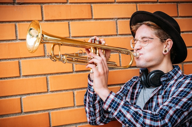 Expressive hipster man hitting trumpet note.