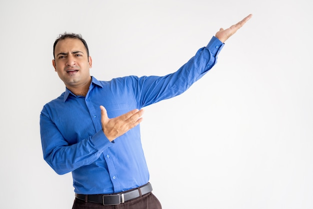 Expressive indian man pointing aside with both hands