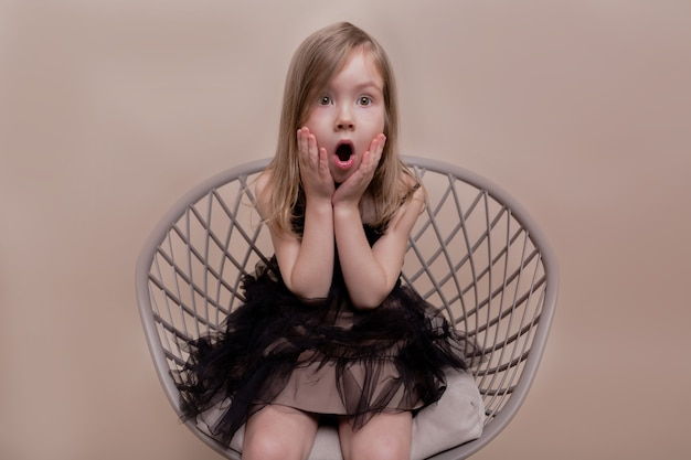 Expressive little charming girl sitting on isolated wall with true surprised emotions
