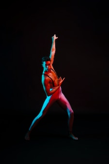 Expressive male ballet dancer in leotard standing in spotlight
