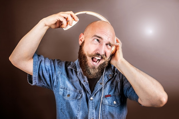 Выразительный мужчина слушает музыку в наушниках