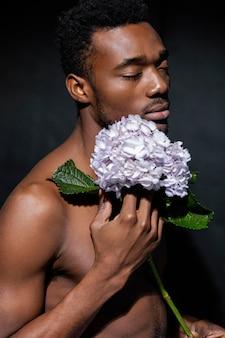 花のクローズアップでポーズをとる表現力豊かなモデル