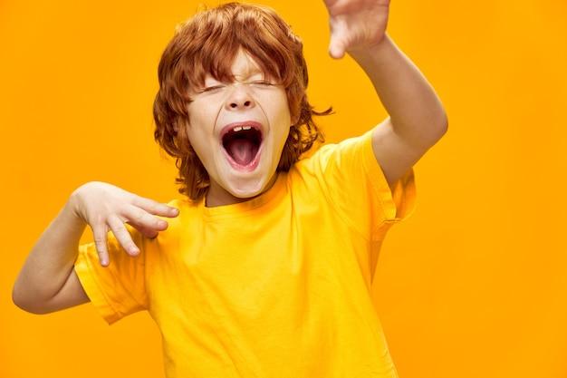 Выразительный рыжий мальчик жестикулирует руками copy space
