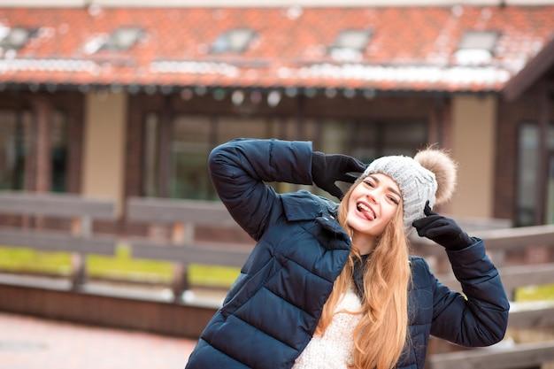 キエフの路上でポーズをとって黒い冬のコートとニット帽を身に着けている表情豊かな赤い髪の若い女性