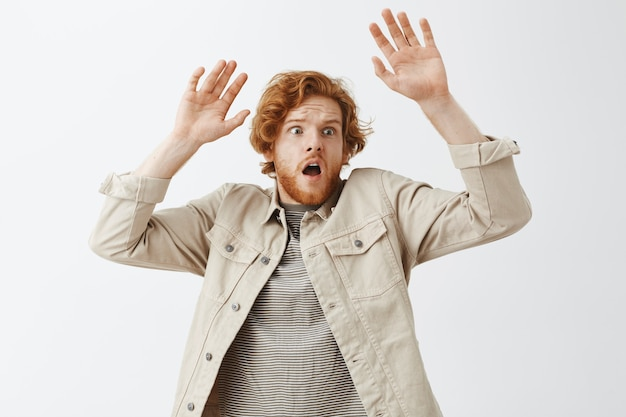 Expressive redhead guy in beige shirt