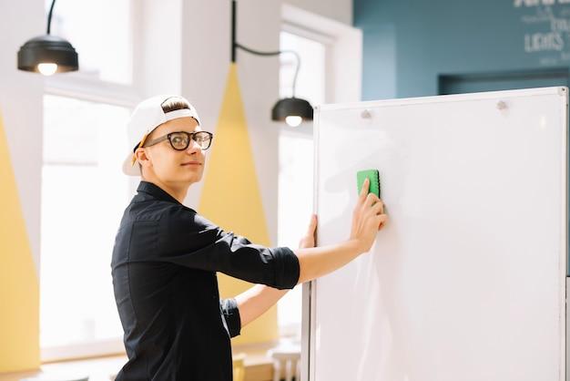 Expressive schoolboy cleaning blackboard